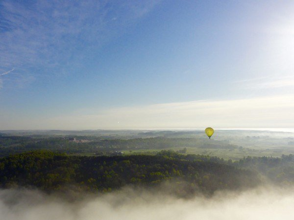A yellow hot air balloon floats over a green landscape covered in mist.