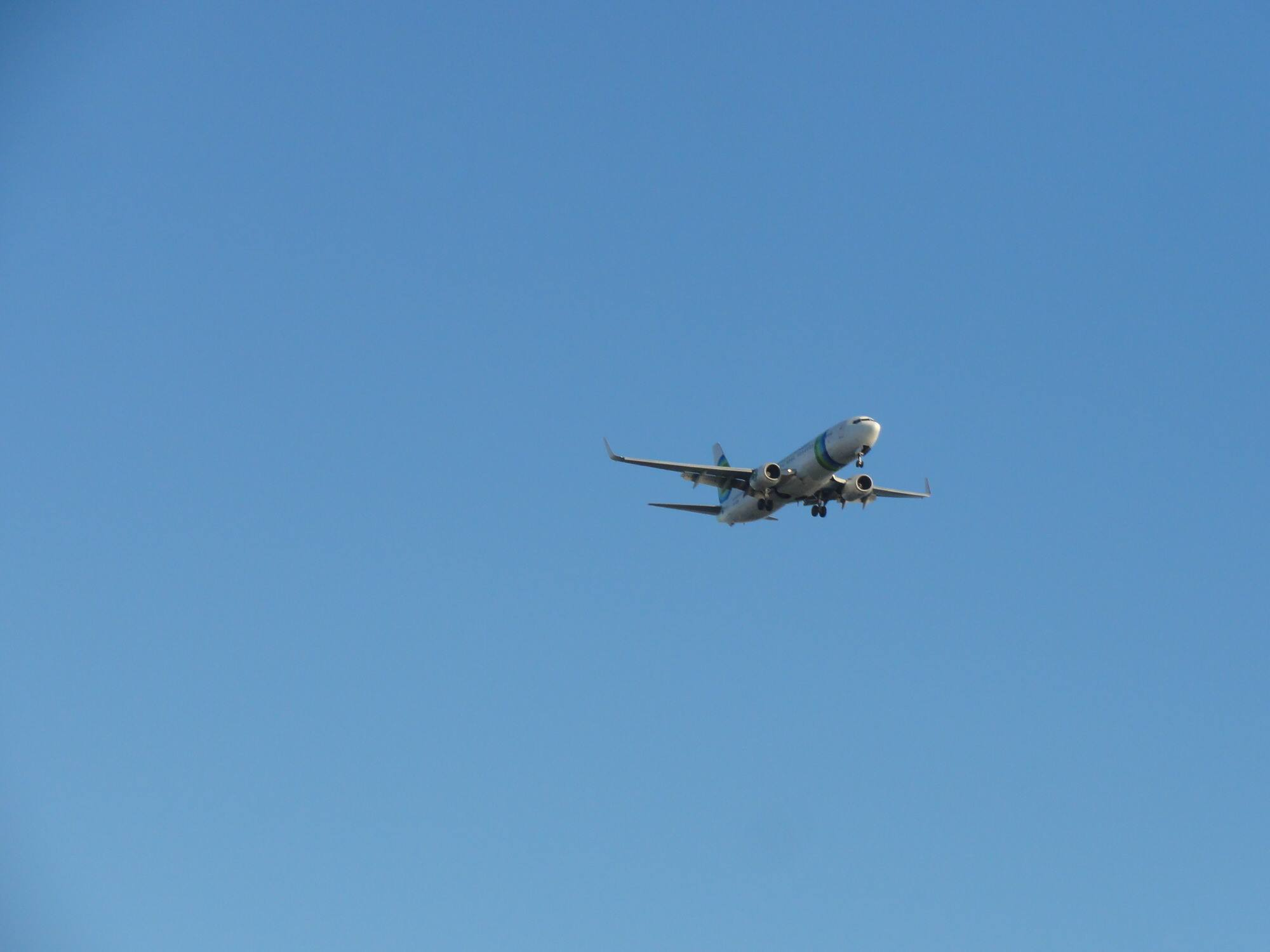 Plane flying in blue sky.