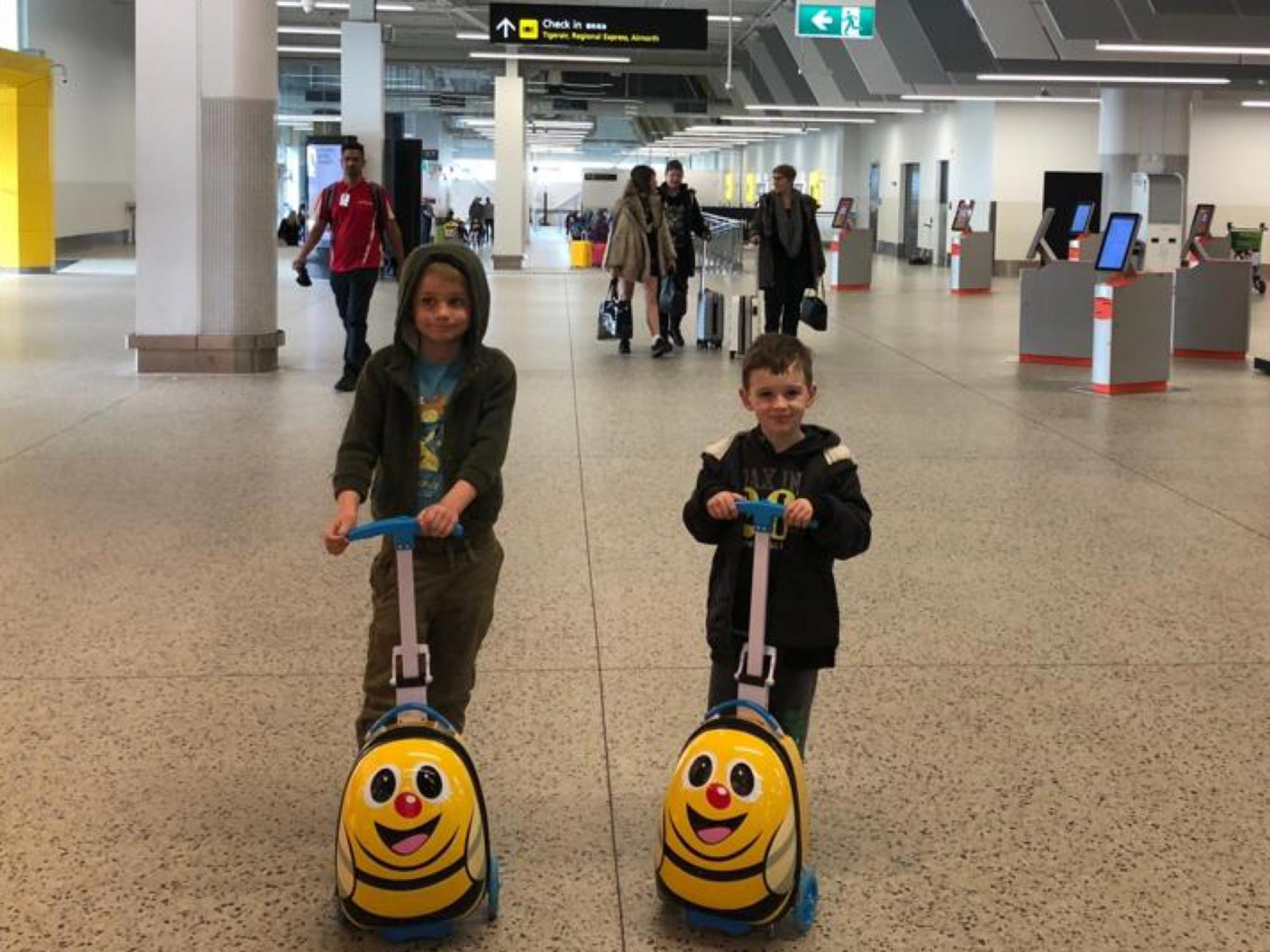 Boys on scooters in airport