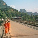Laos travel information - Two young monks on a bridge - square