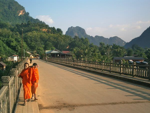 Young monks cross the bridge at Nong Khiaw, Laos