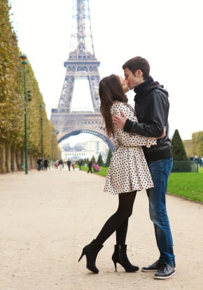 Art of Couples' Travel - Couples Travel Advice - Young romantic couple kissing near the Eiffel Tower in Paris